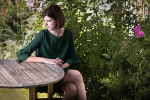 Author Elizabeth MacNeal wearing a green smock dress in her garden