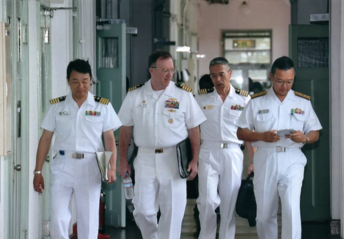 Matt Feely among other naval officers walking down a passageway after an update on Japan's tsunami crisis in March of 2011