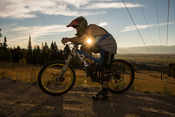 Mountain biker taking a break from riding the trail and jumping in beautiful sunrise light.