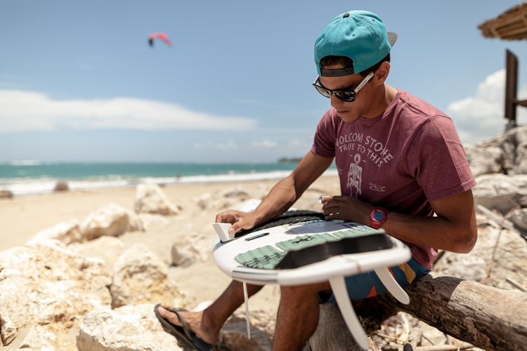 Brandon Sanford waxing a surfboard with Volcom wax at the beach