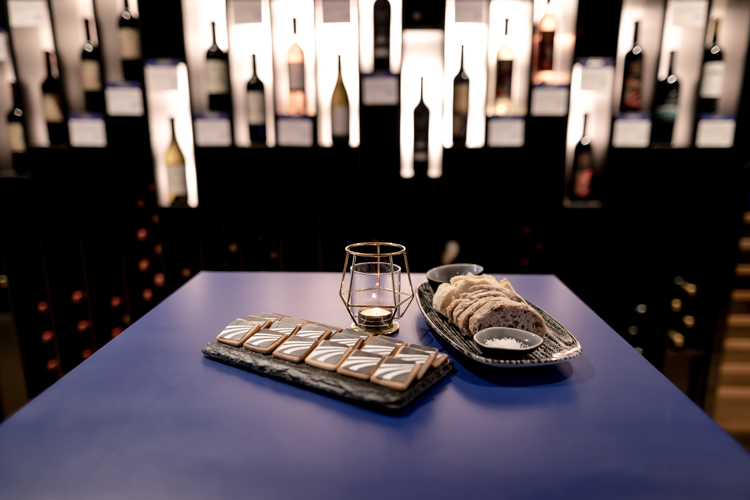 Bread, salt and cookies set up with a candle on a blue table in front of a wine shelf