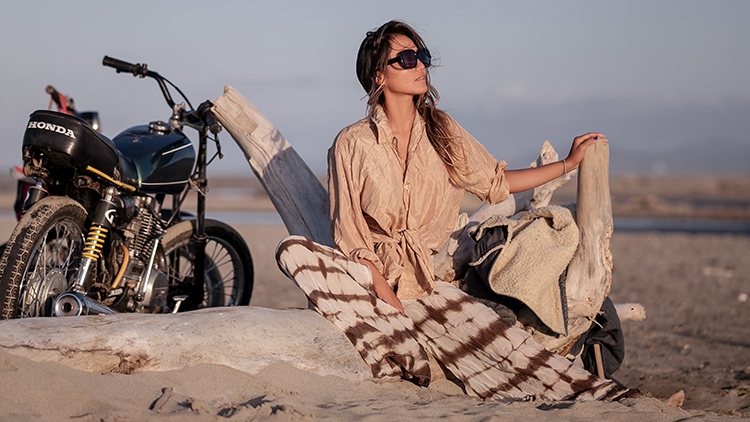 Portrait Paula Rosales next to a motorcycle on the beach