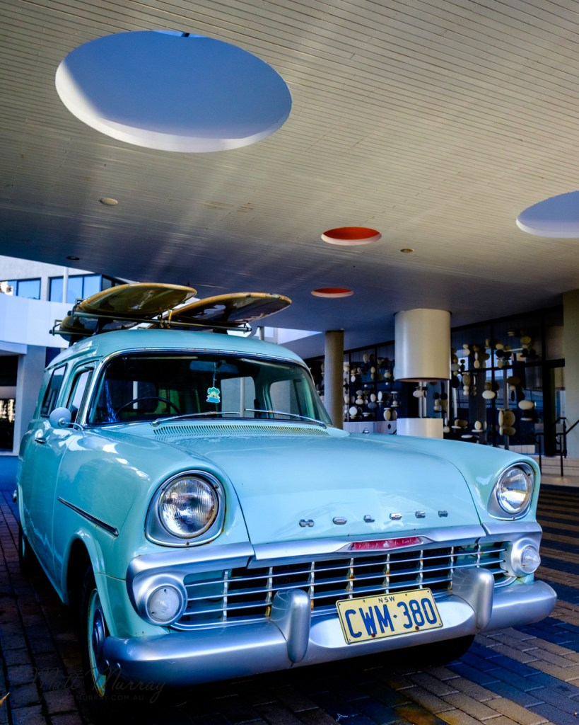 Pastel blue Holden with surfboards on the roof outside the coolest, hippest place in Surfers: QT Hotel