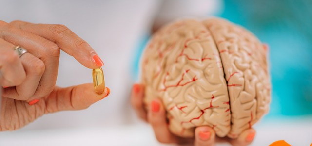 Doctor holding a CBD capsule and a human brain. buy cbd oil in hawaii. CBD hawaii from Maui CBD collective.