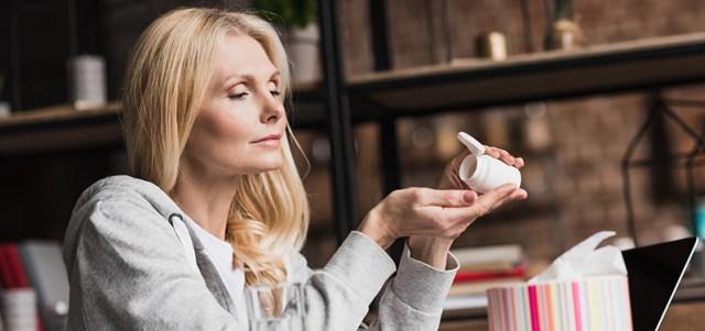 Adult woman dosing CBD capsules. hemp derived CBD edibles natural organic.