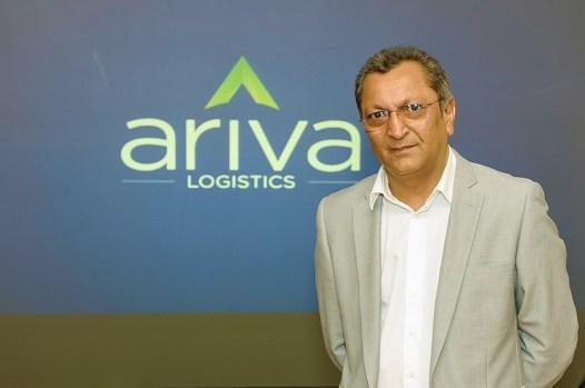 Riaz Esmael, CEO d'Ariva Logistics, devant le nouveau logo de la compagnie.