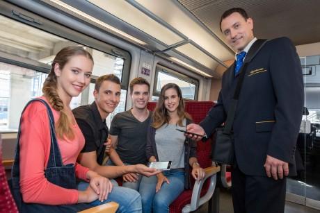Fiatalok e-vonatjegyet mutatnak meg a jegyvizsálónak