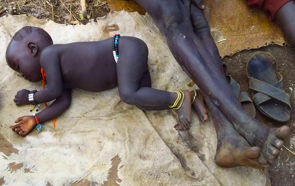 Mursi baby sleeping outdoors
