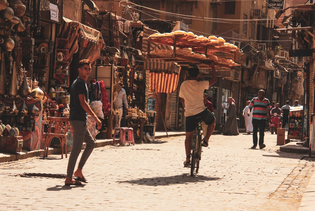 A bread seller cycling down the Muizz Street