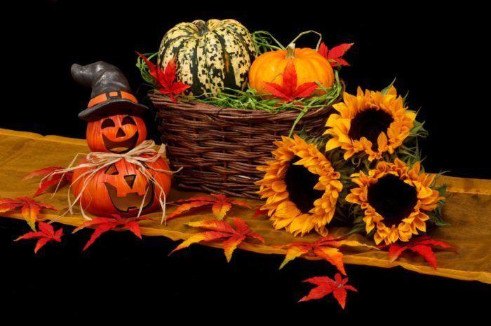 Calabaza de Halloween con cesto lleno de calabazas y girasoles sobre una mesa