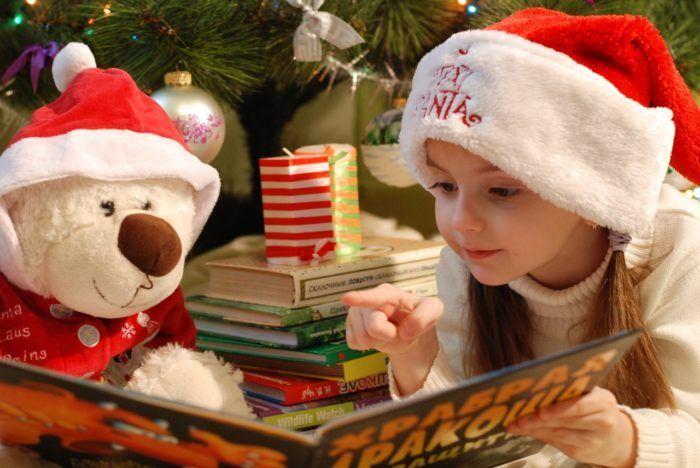 niña leyendo cuentos infantiles con un gorro de navidad