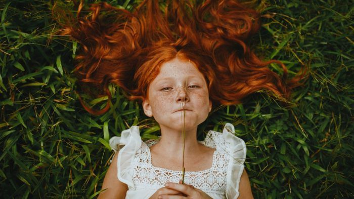 niña practicando mindfulness tumbada sobre el césped