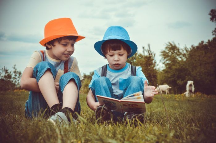 Dos niños disfrutan de leer en vacaciones al aire libre