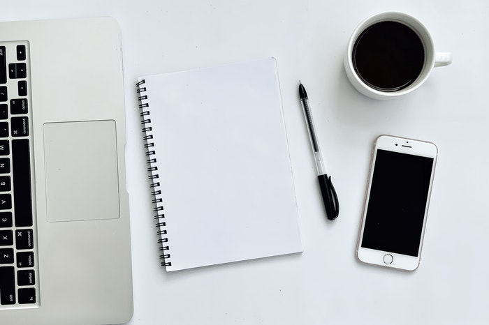 Cómo planificar contenido con portátil, teléfono móvil y agenda minimalista en blanco