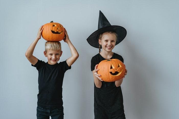 Cuentos sobre Halloween para trabajr el miedo y dos niños felices con dsifraces de Halloween y calabazas