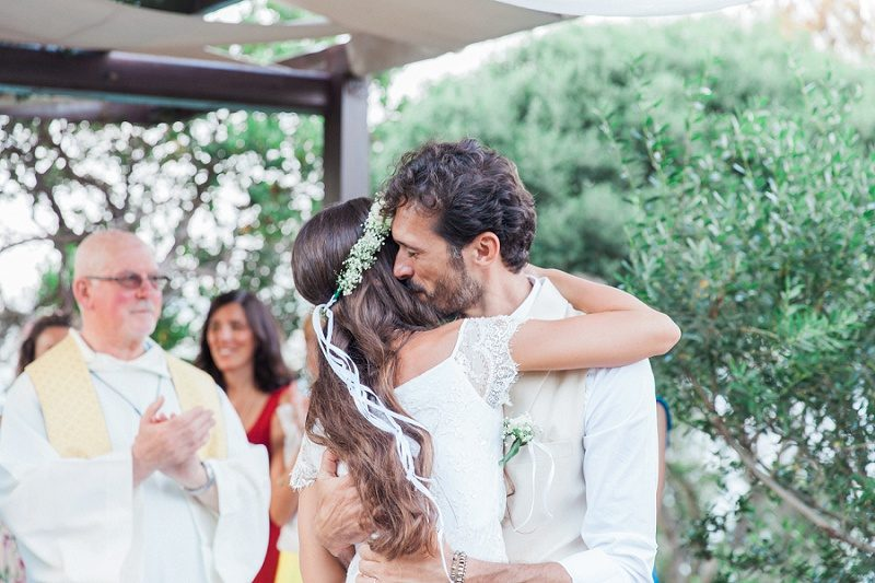 Bride and Groom Hugging After their Bohemian Garden Wedding Ceremony