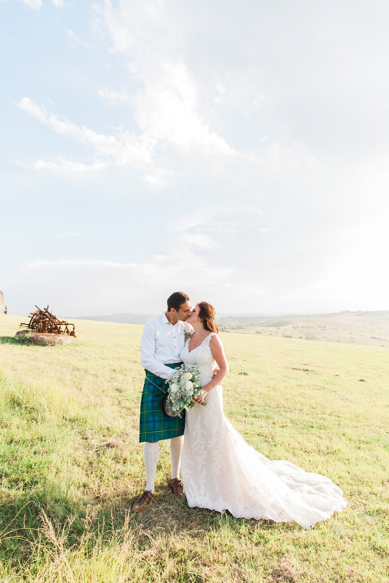 Bride and Groom Sharing a Kiss During Thier Pistachio and White Wedding