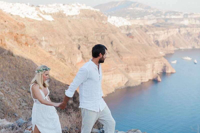 Newlyweds Walking Along the Edge of the Caldera in Santorini
