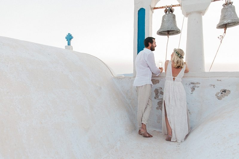 Newlyweds on a Church Roof After Their Sunset Elopement In Santorini