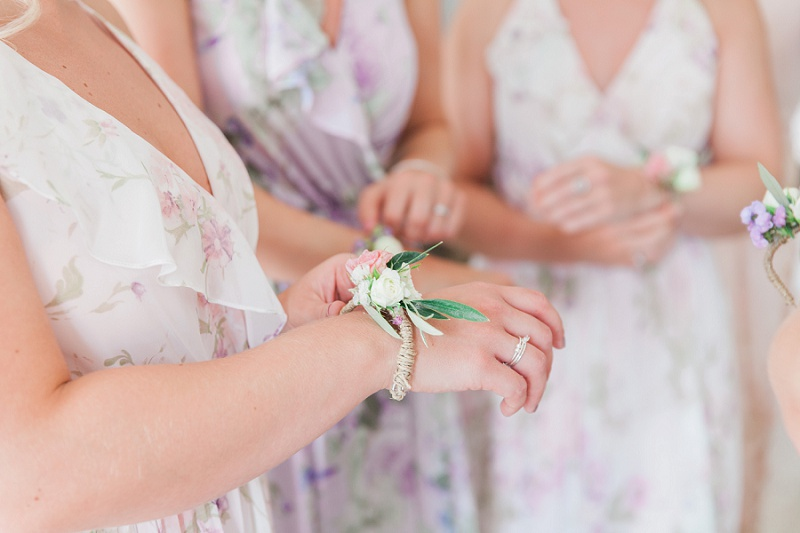 Bridesmaids putting on their flower bracelets at brides villa