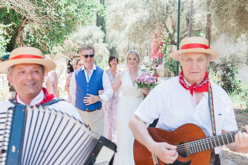 Bride and her father walking to the ceremony while being serenaded by a trio of Greek musicians