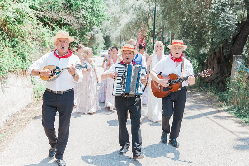 Trio of Greek musicians in full song as they serenade the bridal party to the ceremony