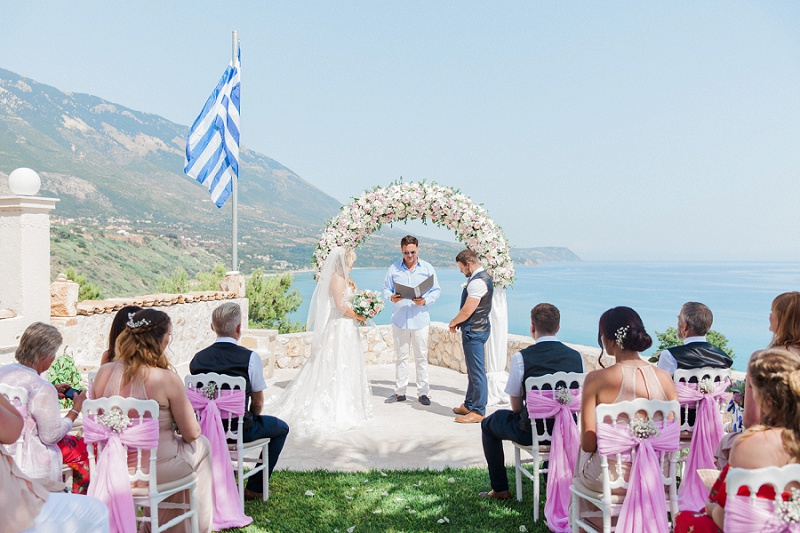Bride and groom standing with the celebrant under a pink and white floral arch.