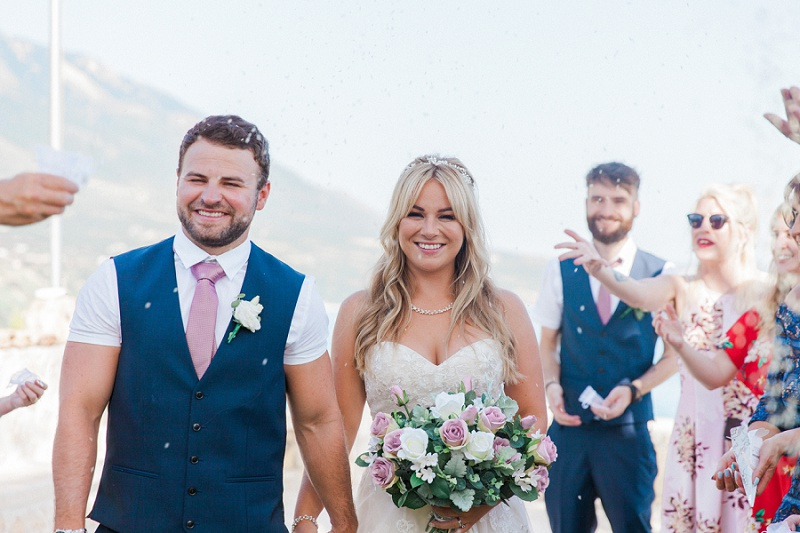Smiling couple walking out of their ceremony under a shower of confetti