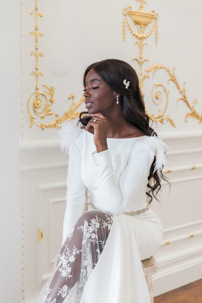 Black bride wears a Cynthia Grafton-Holt gown with feather sleeves
