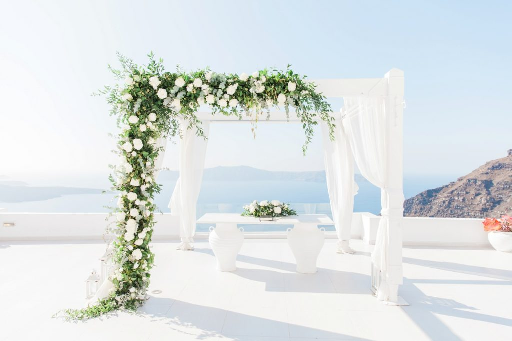 White and foliage wedding arch with flowers by Betty Flowers Santorini at Dana Villas Infinity Suites