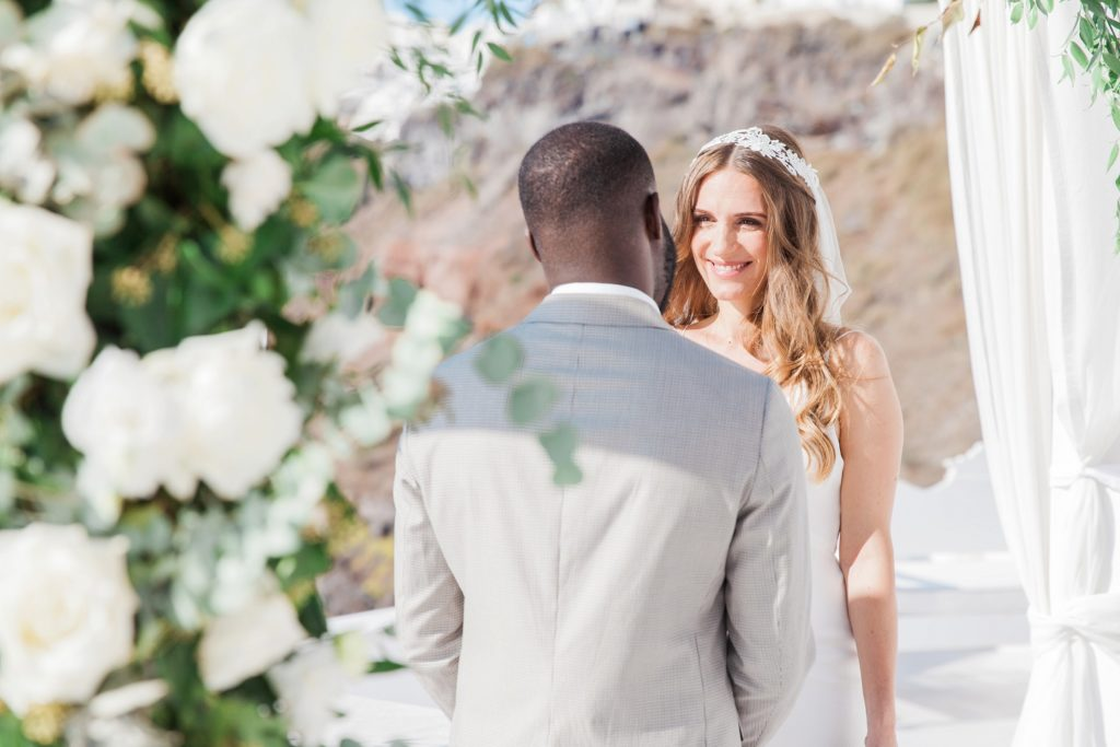 Bride smiles at the groom during their elopement ceremony in Santorini