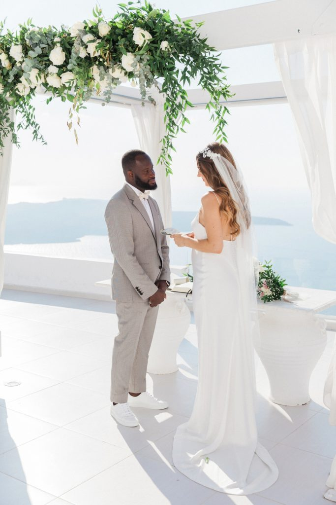 Bride and groom exchange vows under a white and green wedding arch at Dana Villas Santorini