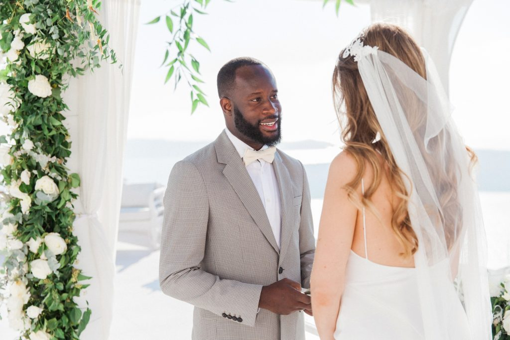 Groom smiles as the rings are exchanged during their Santorini elopement
