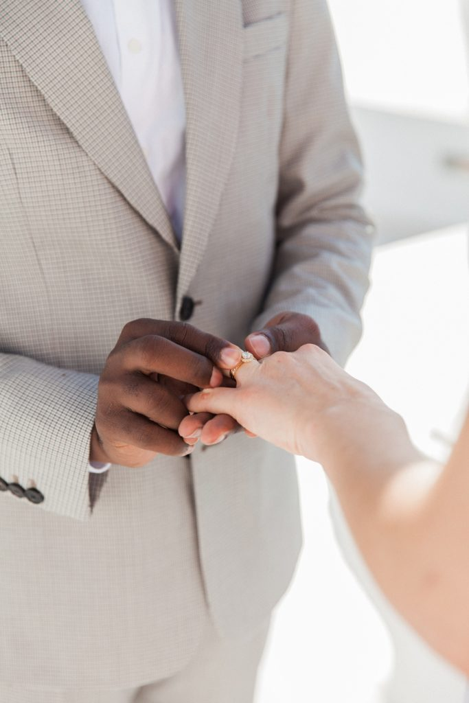 Close up of the groom placing a ring on her brides finger during their elopement in Santorini