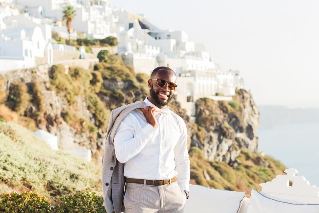 Portrait of a happy groom against the Santorini houses and the cliffs