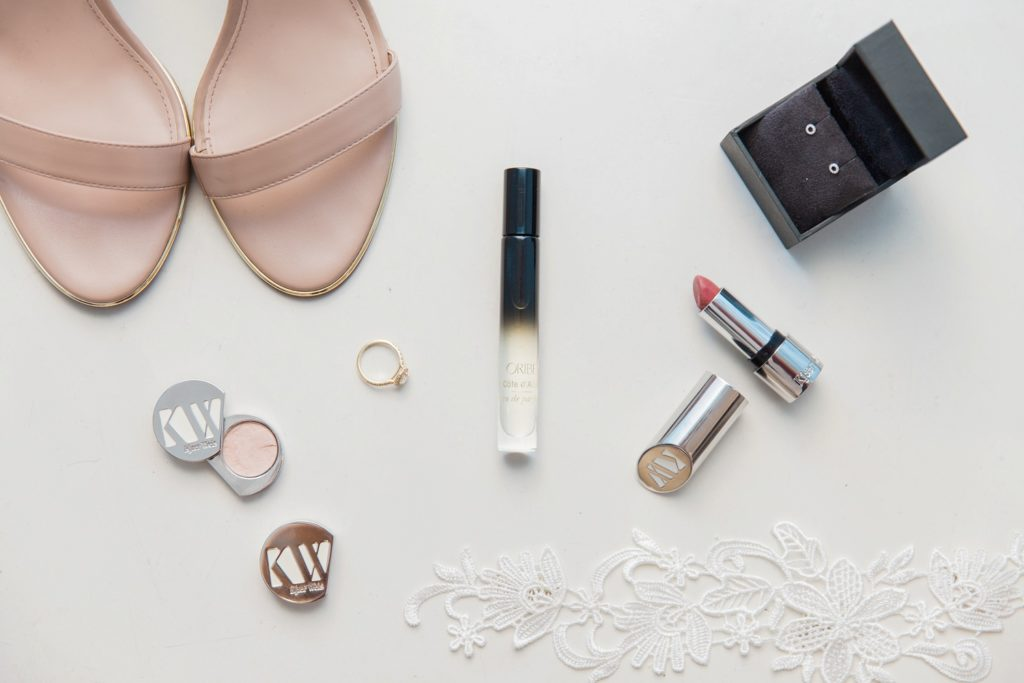 Flatlay of the brides details featuring Carvela heels, Oribe fragrance, jewellery and make-up