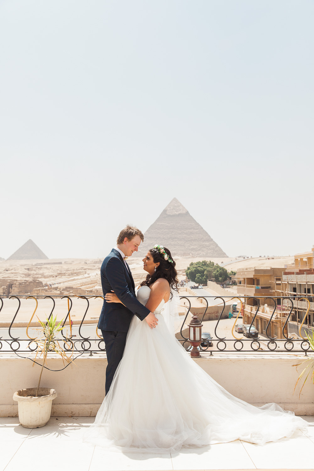 Bride and groom standing in front of the Pyramids of Giza at their destination wedding in Egypt
