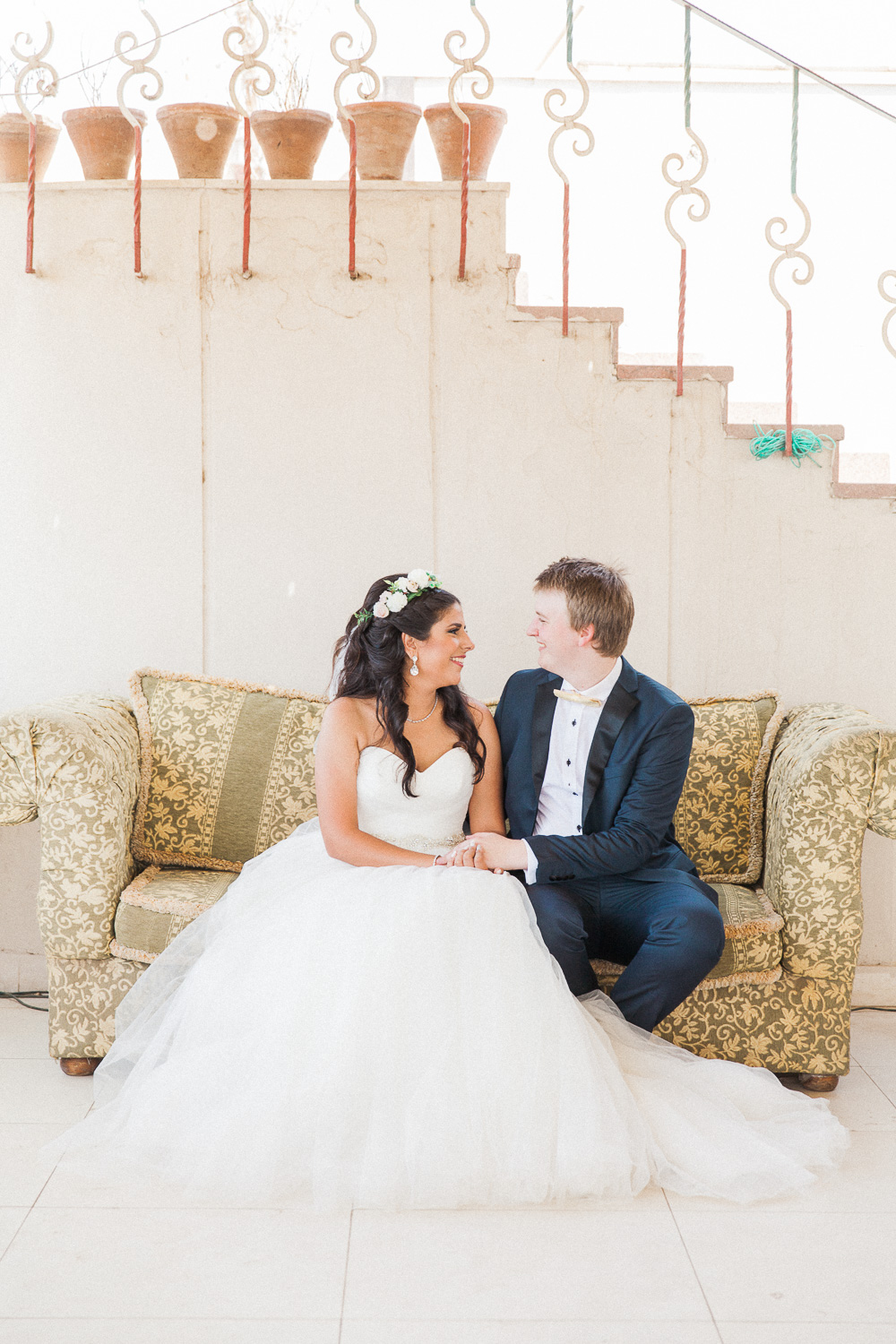 Bride and groom sitting on a sofa during their destination wedding in Cairo, Egypt