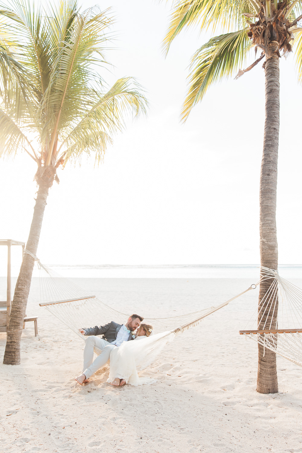 Bride and groom in a hammock at their destination wedding in Mauritius at Dinarobin Beachcomber Golf Resort and Spa