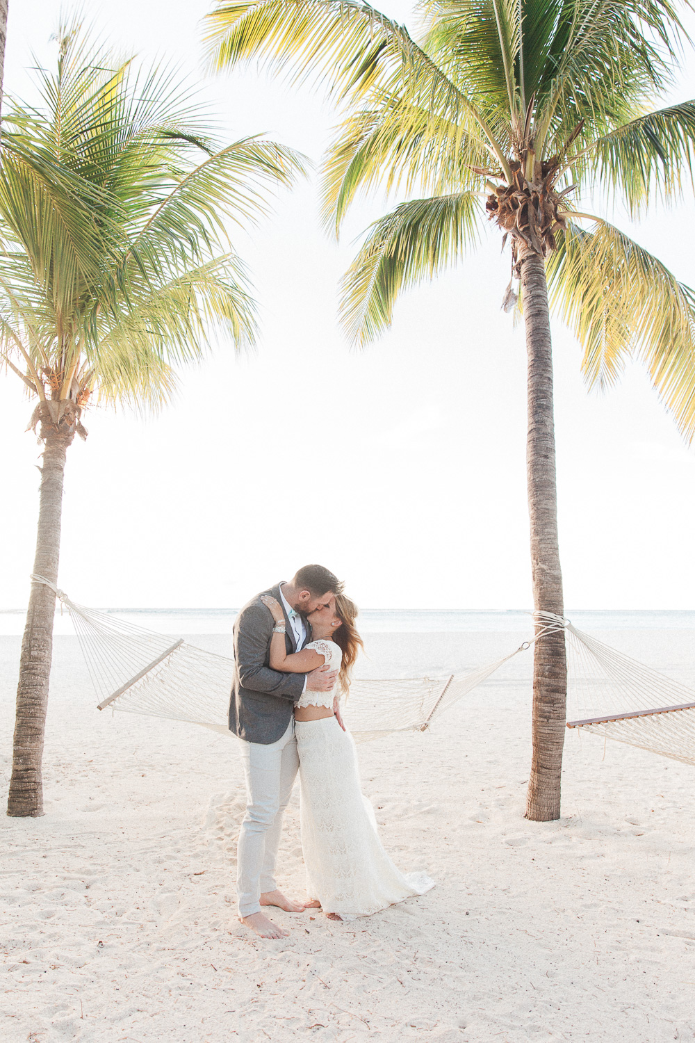Bride and groom kissing under the palm trees at their destination wedding in Mauritius