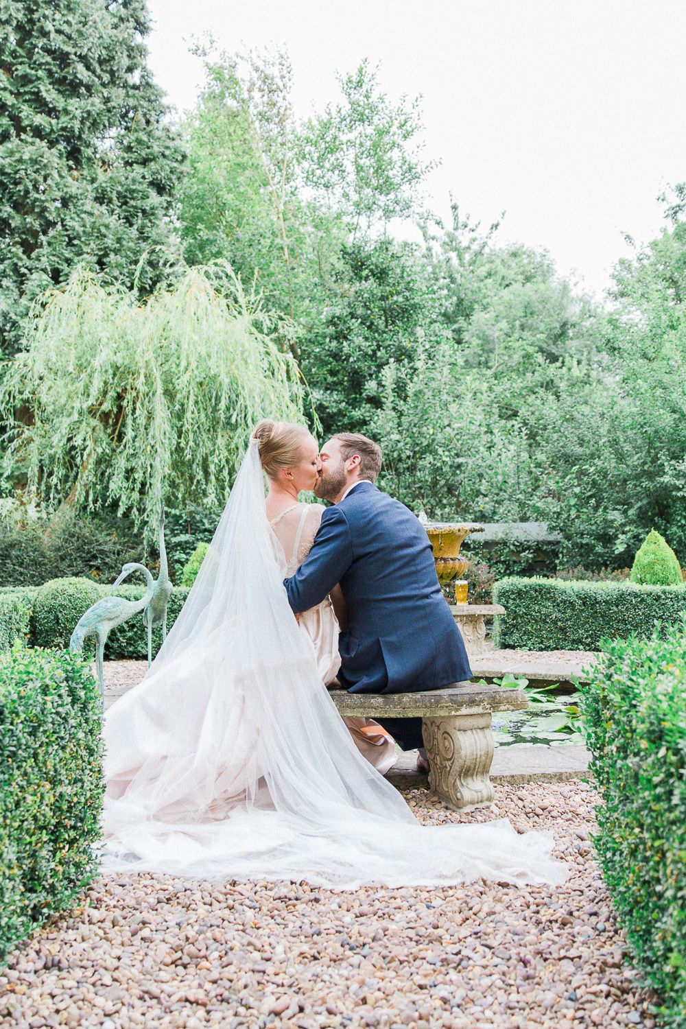 Bride and groom kissing on a bench at their English garden wedding