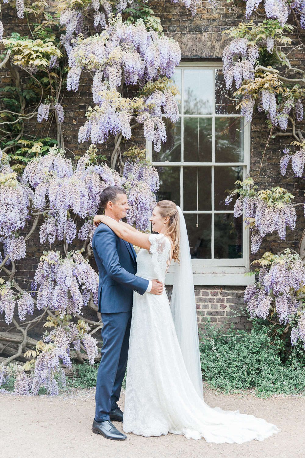 Bride and groom against a backdrop of whisteria at Fulham Palace wedding venue in London