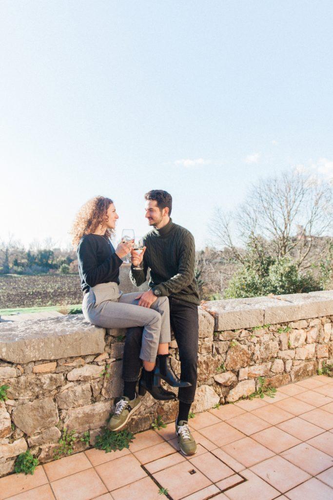 Couple enjoy a wine in the sunshine in Sermoneta, Italy