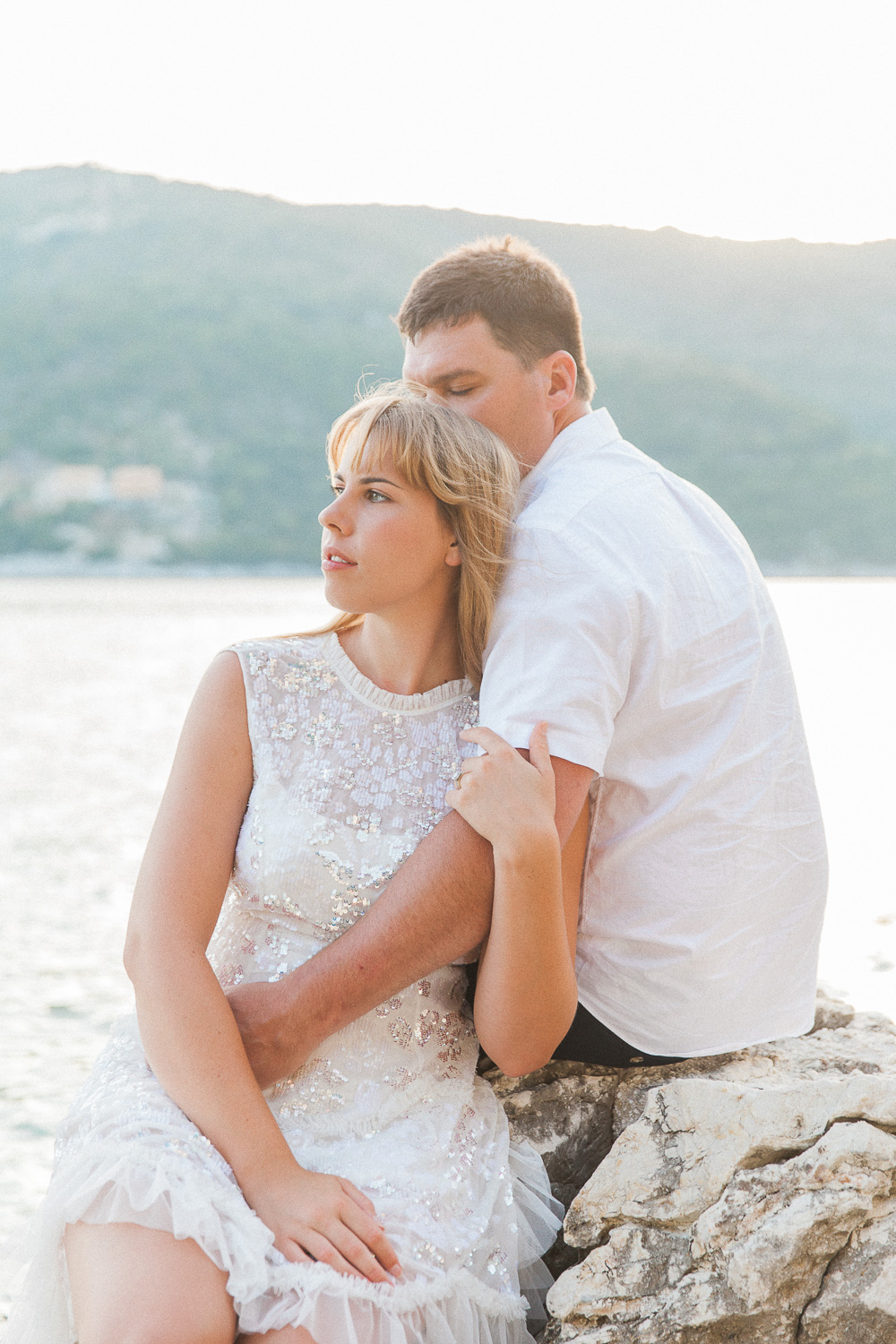 Couple sitting together on a rock over looking the sea in Lefkada, Greece