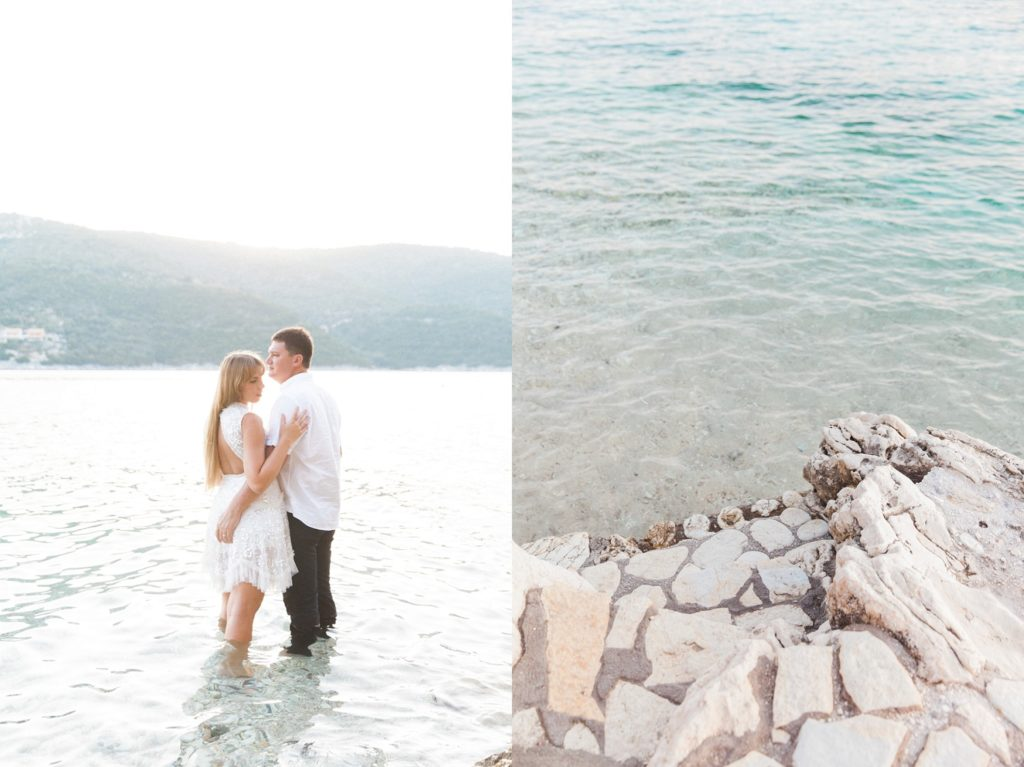 Couple standing in the sea next to stone steps at the San Nicolas Resort Hotel in Lefkada