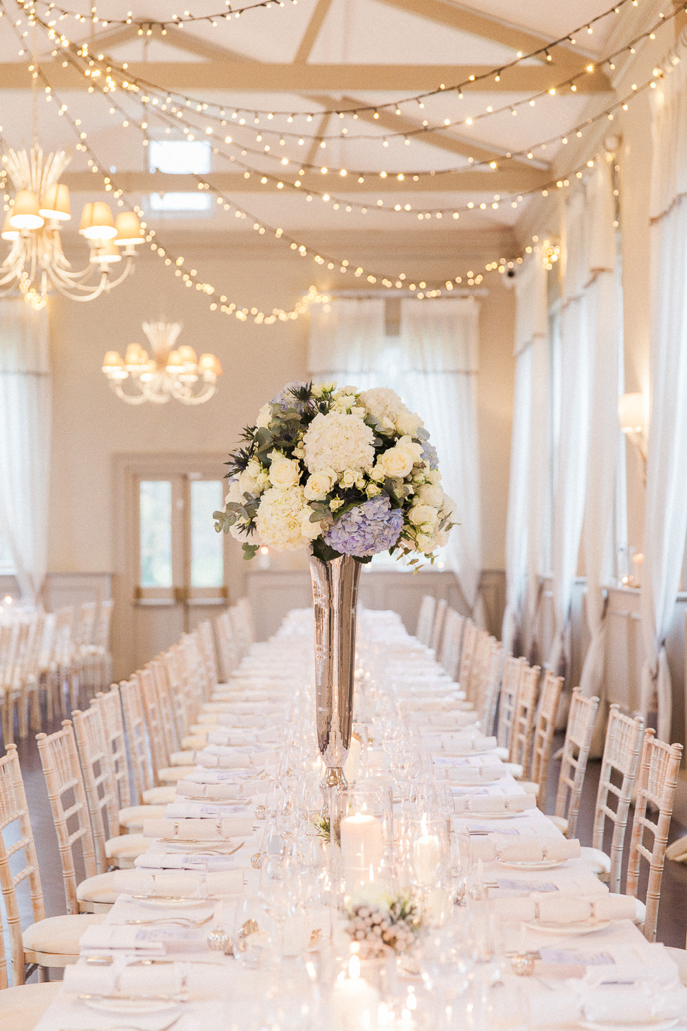 Reception table with blue and white centerpiece and fairy lights at Morden Hall wedding venue in London