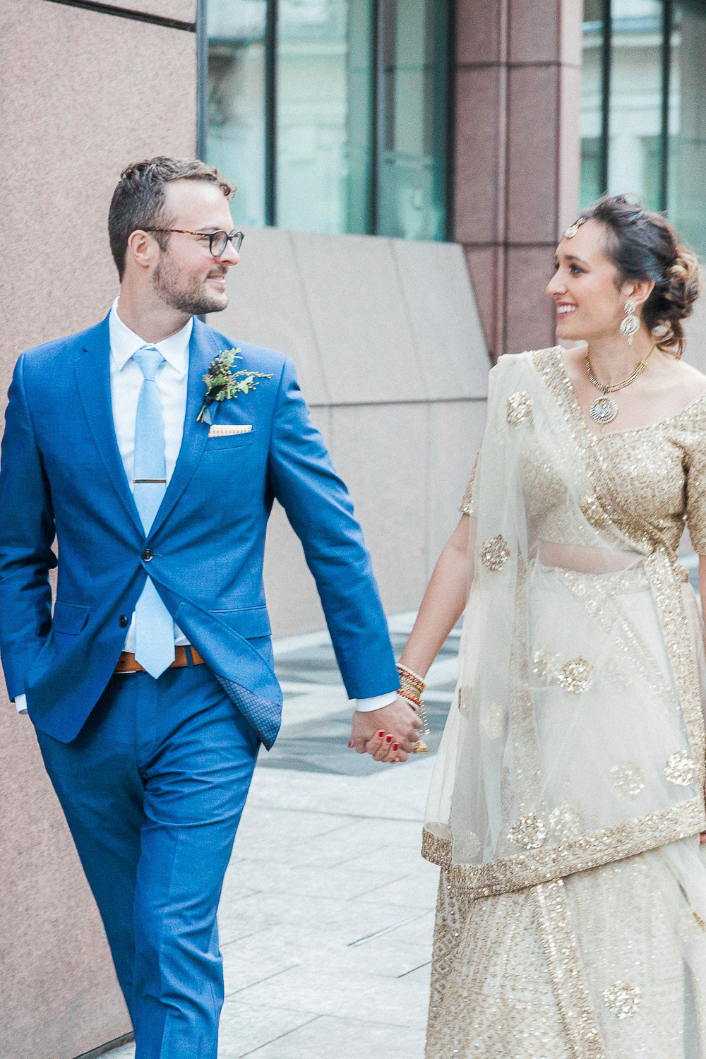 Bride and groom hold hands during their multicultural London wedding