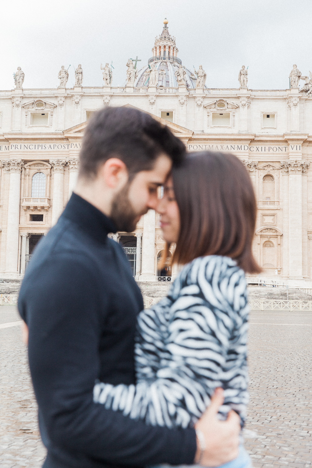 Couple hugging in front of Sait Peter's Basilica in Rome, Italy