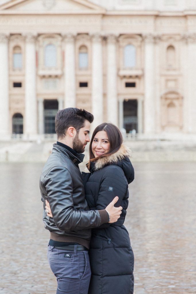 Couple hug during their Rome couple photography session at St. Peter's Basilica