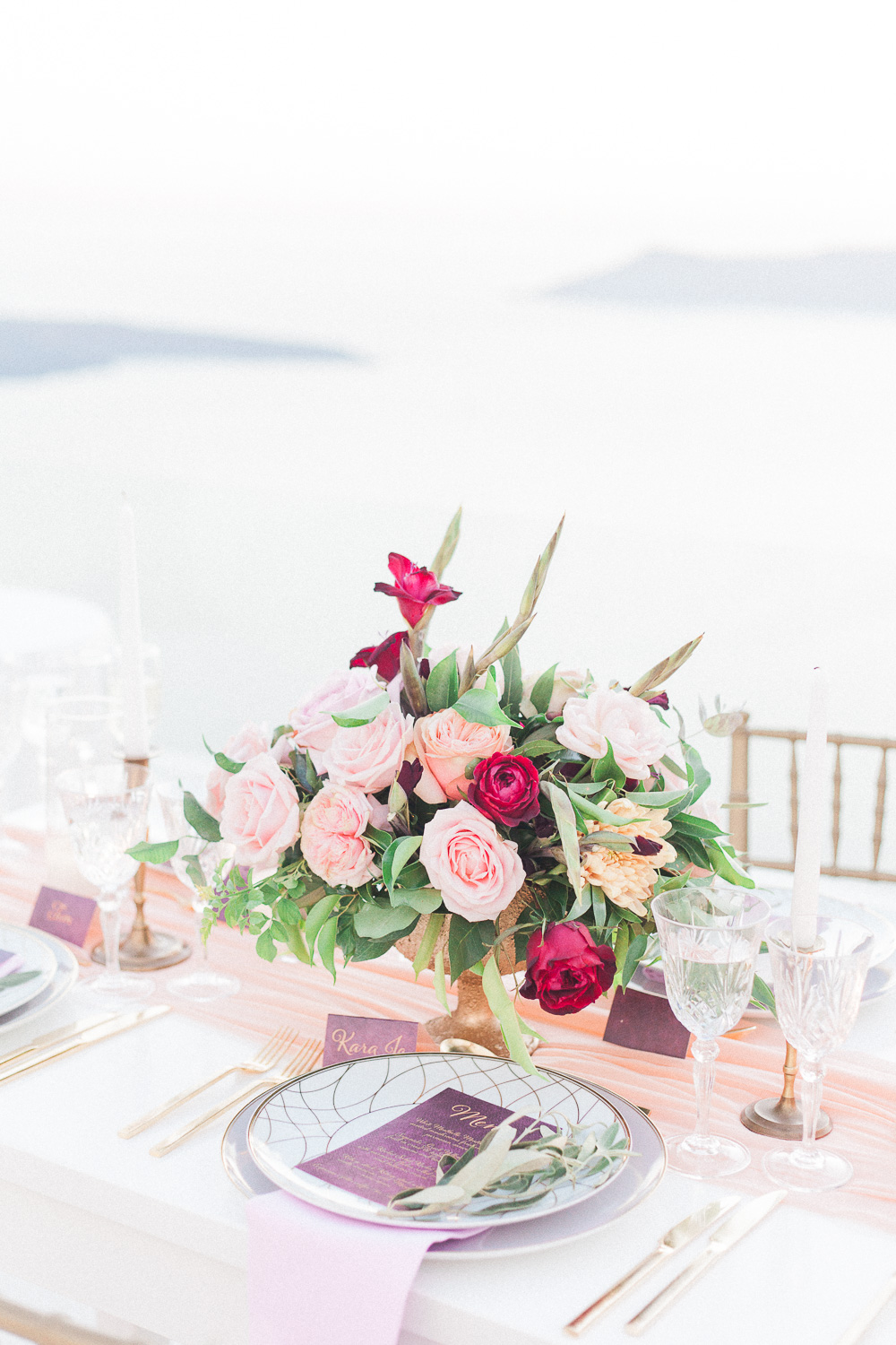 Pink, peach and red centrepiece and table decor at Dana Villas Santorini wedding